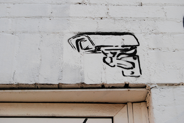 Surveillance camera stencil art. Photo by Paul Lowry via Flickr (CC BY 2.0)